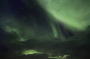 The Northern Lights shine through clouds